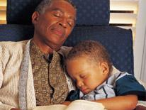 Older man asleep in an armchair holding a sleeping child